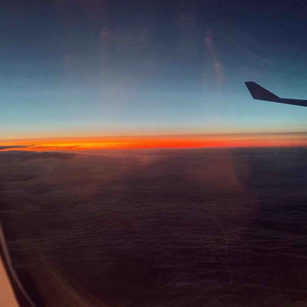 Airplane window view, orange sunset against blue sky