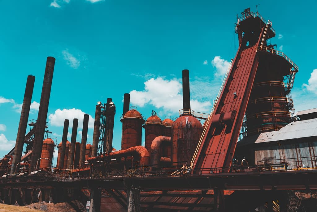 Large red furnaces against blue sky with white clouds