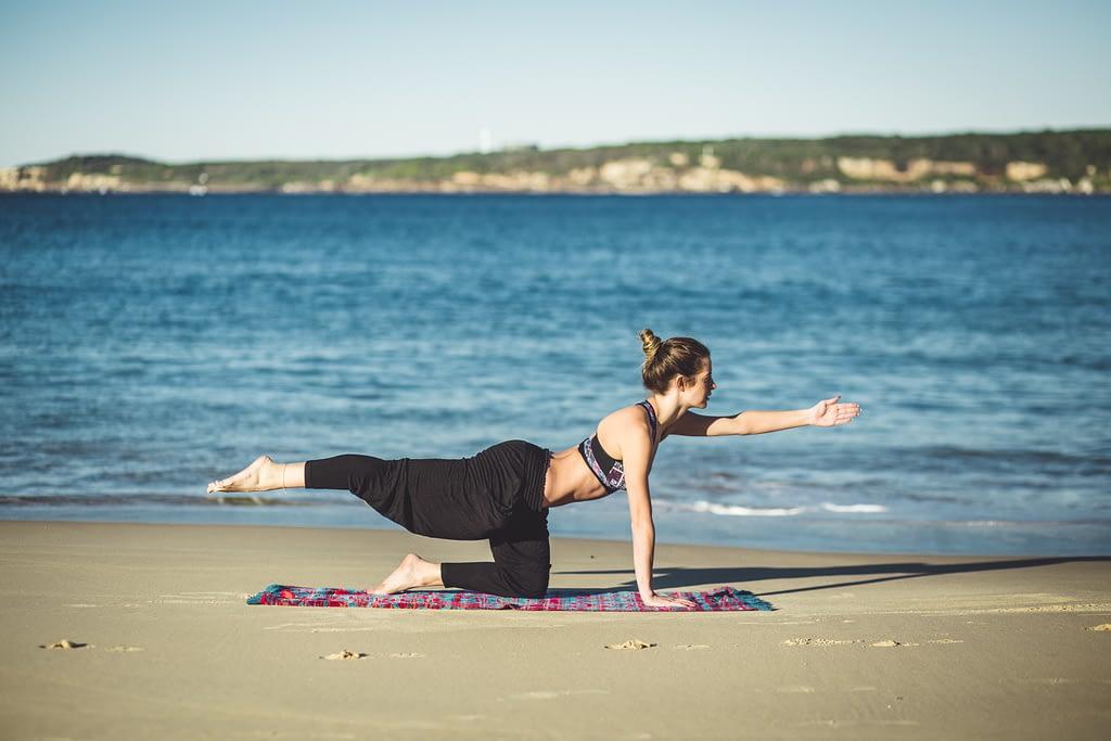 Woman doing a quadruped arm/leg raise on the beach.