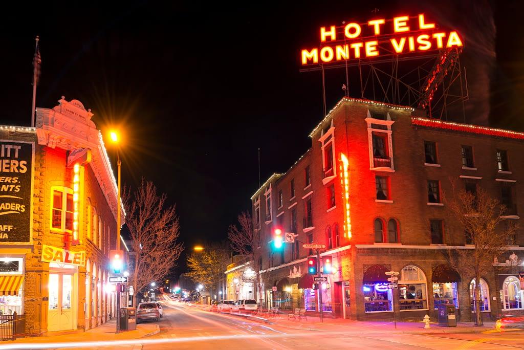 Neon sign that reads Hotel Monte Vista, street scene at night