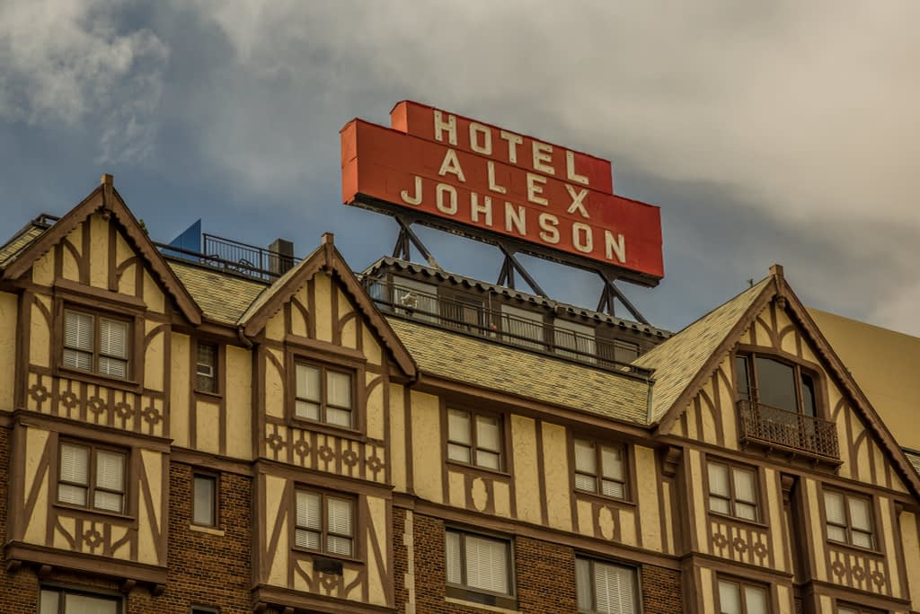 Close-up of red Hotel Alex Johnson sign on top of brick and yellow building