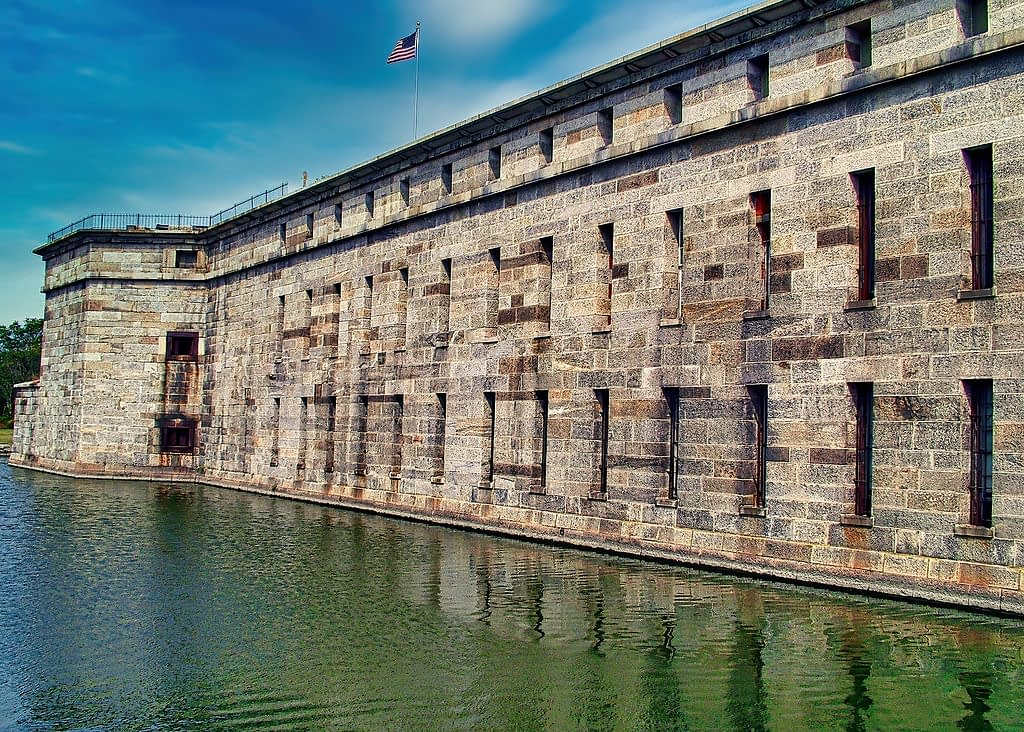 Fort with weathered bricks surrounded by a moat, American flag on top