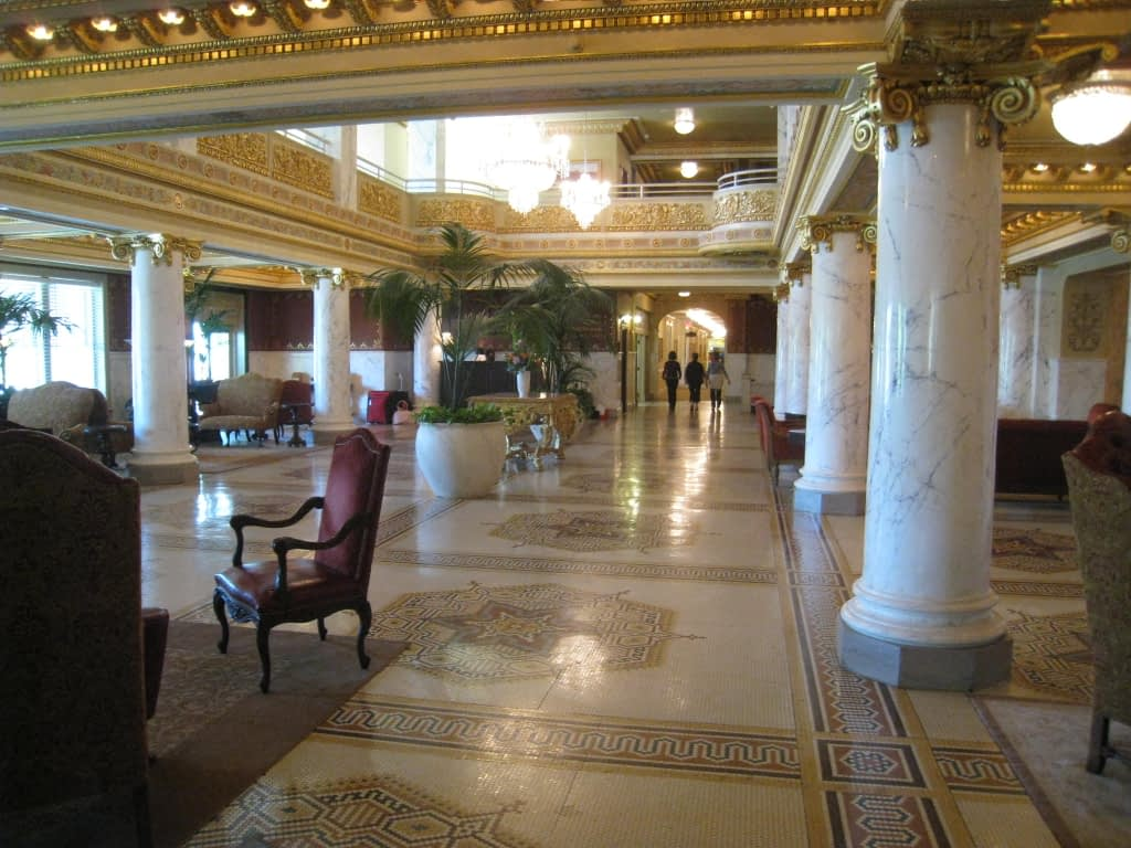 Inside of hotel lobby with white and gold decor