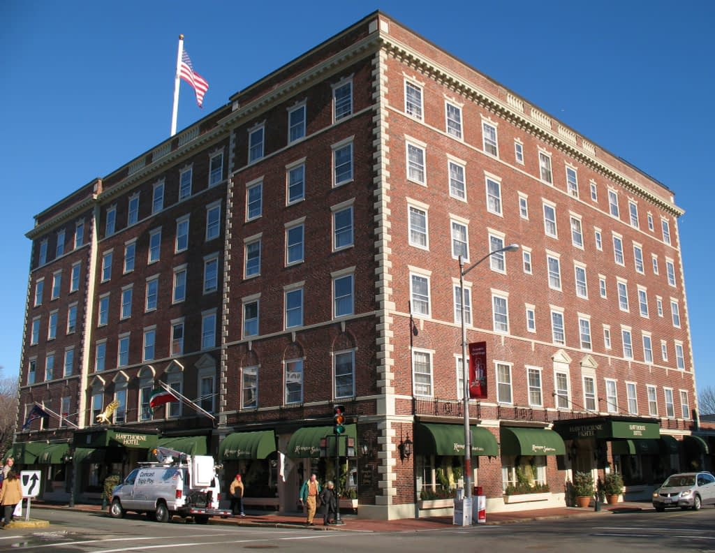 Large brick building with American flag on top, green awnings