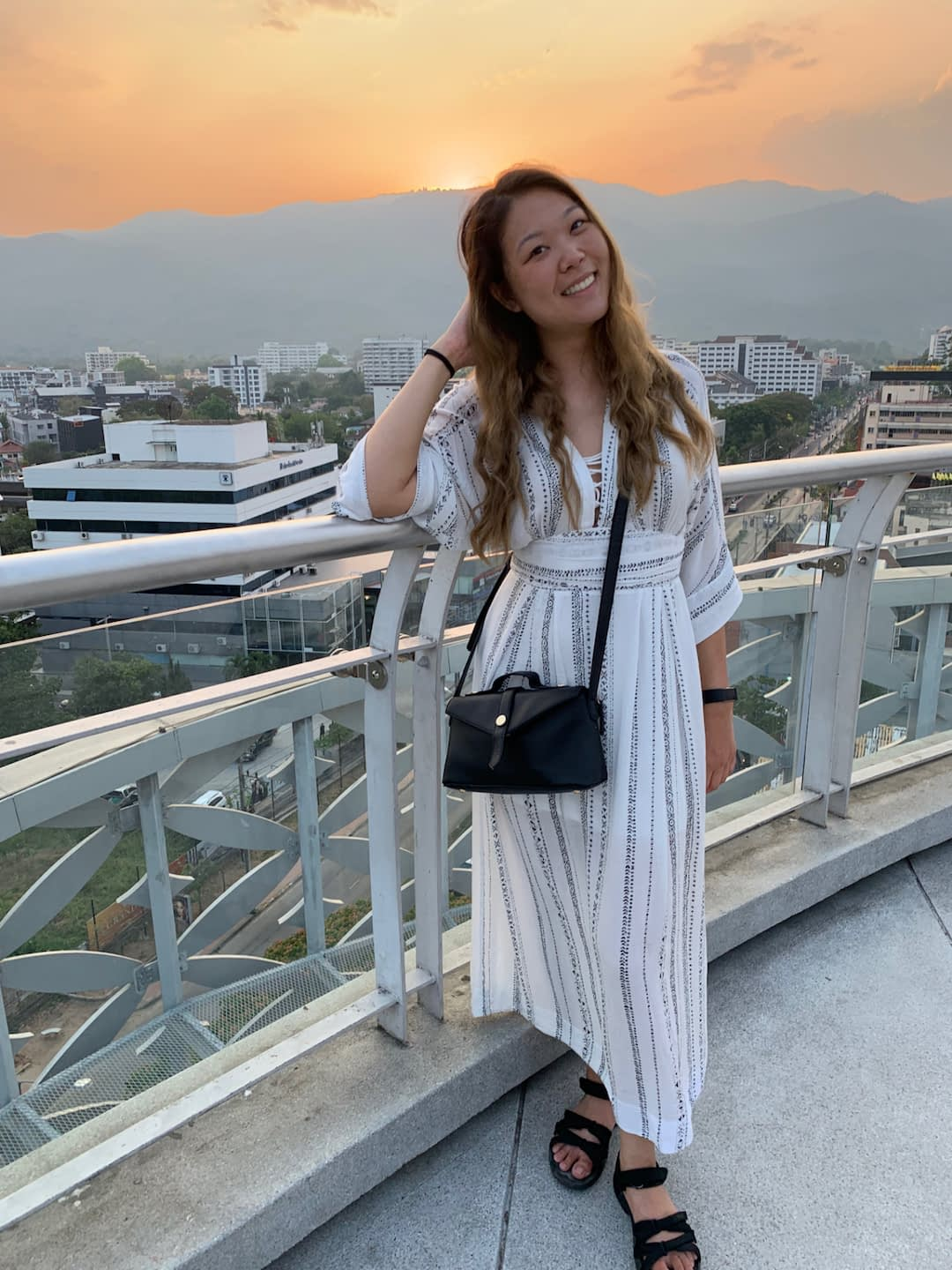 Girl wearing a white dress, smiling with mountains and an orange sunset behind her