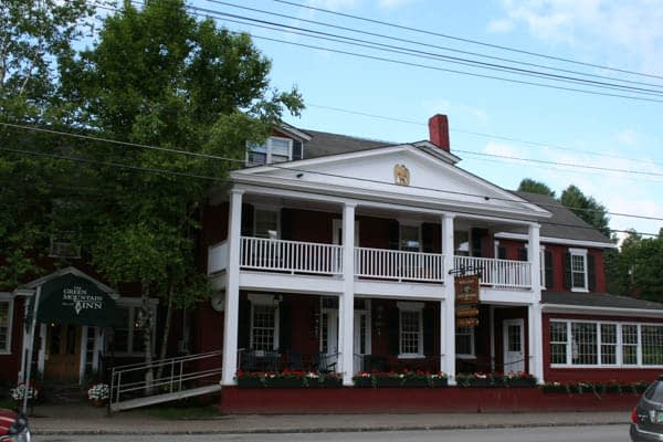 Brick and white building on street with green awning that reads The Green Mountain Inn