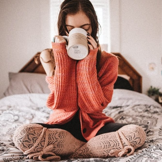 Woman sitting on bed sipping out of a mug