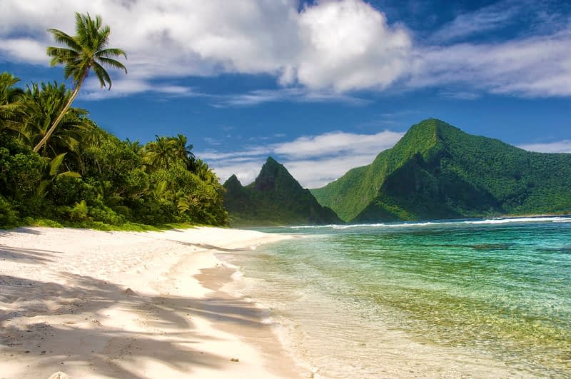 Beach in American Samoa, clear blue-green water lapping against light sand with green mountains in the back